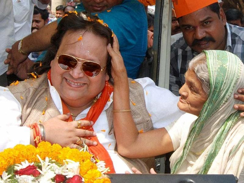 Singer and BJP candidate Bappi Lahiri seeks blessings from an elderly woman during his election campaign at Bally in Sreerampore constituency. (PTI photo)