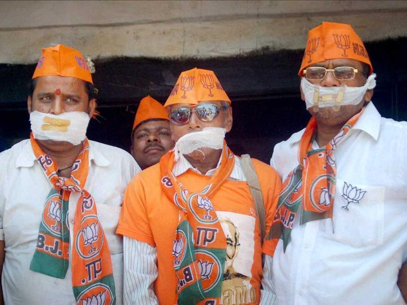 BJP workers cover their mouths during Aam Aadmi Party's election campaign in Varanasi. (PTI Photo)