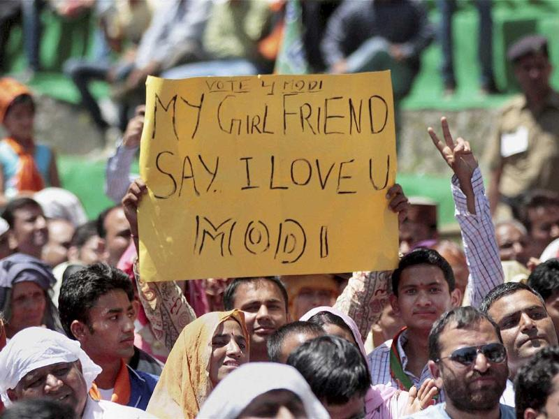 A BJP supporter holds placard praising Modi at the BJP election rally in Palampur. (PTI Photo)