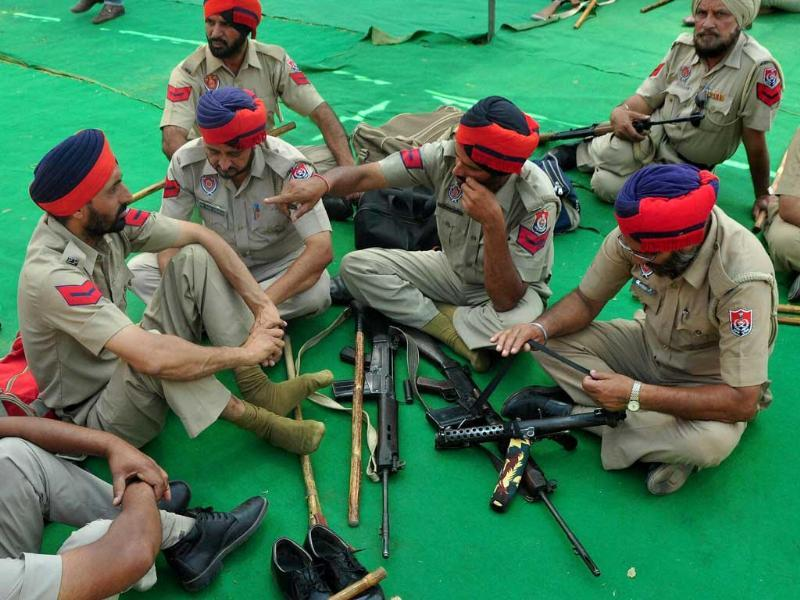 Punjab policemen take rest before going for election duty at Polo Ground in Patiala. (PTI Photo)