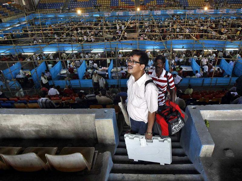 An election official carries an electronic voting machine at an election material distribution centre ahead of the seventh phase of the general election at Howrah district of West Bengal. (Reuters Photo)