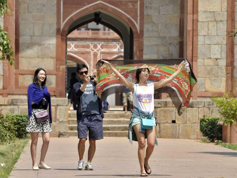 Foreign tourists from South Korea take precautions against the hot weather at Humanyun's Tomb in New Delhi, India. (Sushil Kumar/HT Photo)
