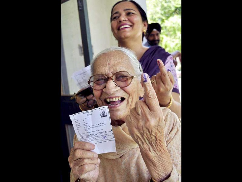 An elderly voter shows her inked finger after casting her vote for the Lok Sabha polls at a Polling station in Patiala. (PTI Photo)