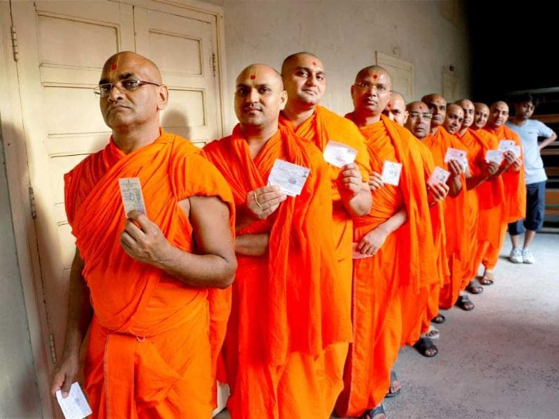 Swaminarayan Temple priests show their ID cards as they wait in a queue to cast their vote during Lok Sabha elections in Ahmedabad. (PTI Photo)