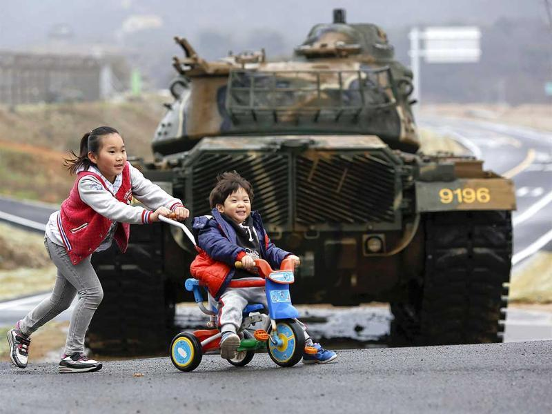 Children play in front of a tank on the island of Baengnyeong, which lies on the South Korean side of the Northern Limit Line (NLL), in the Yellow Sea. (Reuters)
