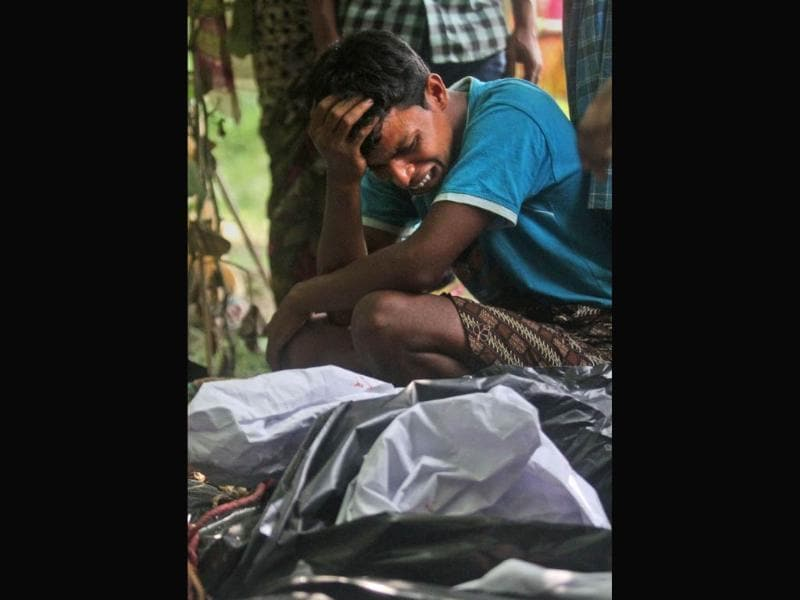 A man cries near the body of a relative, killed in ethnic violence, at a burial ground at Narayanguri village, in the northeastern state of Assam. (AP Photo)