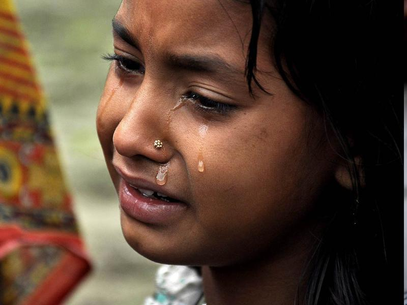 A child mourns the death of a relative in the village of Narayanguri, around 200 km west of Guwahati. (AFP Photo)