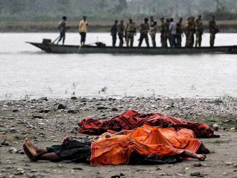 Bodies of people killed in ethnic violence lie covered in the rain on the banks of the River Beki, as security officers patrol the area on a boat at Khagrabari village, in the northeastern state of Assam. (AP Photo/Anupam Nath)