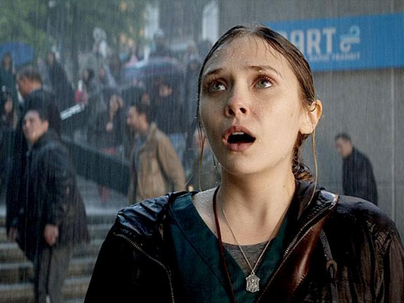 Elizabeth Olsen looks terrified as she crosses paths with Godzilla in new film stills.