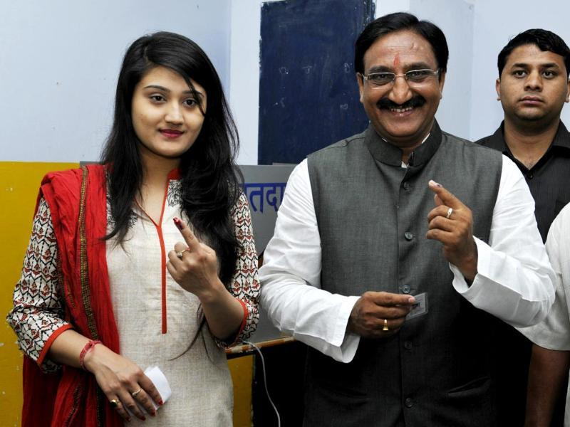 Former Uttarakhand CM Ramesh Nishank Pokhriyal and his daughter showing their inked finger after casting their vote in Dehradun. (HT photo/Rishi Ballabh)