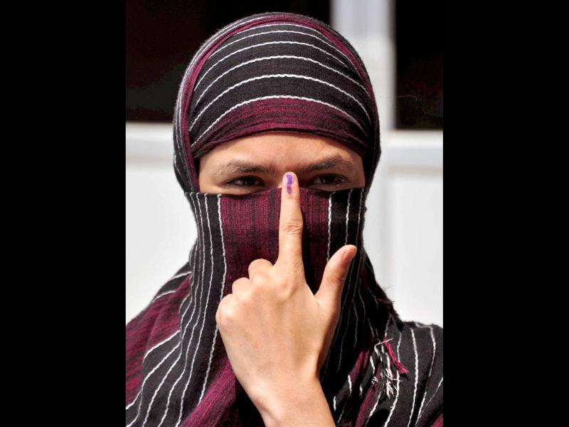 A Muslim woman shows her ink marked finger after casting vote for 8th phase of Lok Sabha election in Allahabad. (PTI photo)
