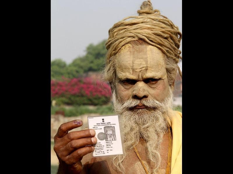 A sadhu displays his inked finger and voter card after casting vote in Ayodhya. (AFP Photo)