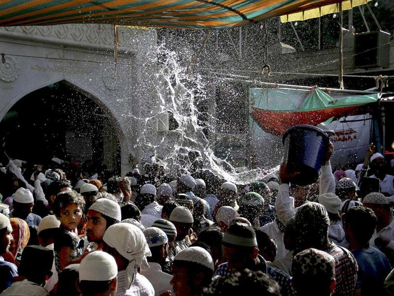 Devotees get showered with perfumed water during the Urs festival at the shrine of Sufi saint Khwaja Moinuddin Chishti in Ajmer. (PTI Photo)