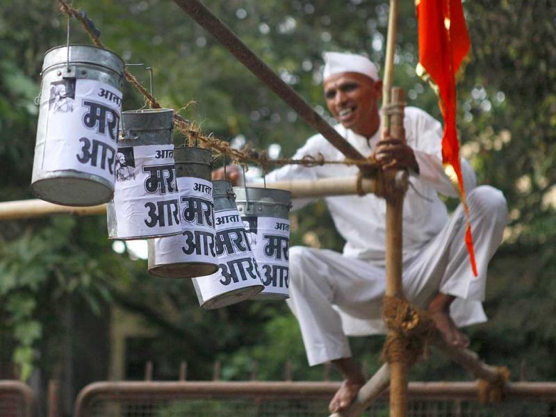 A Mumbai Dabbawaala hangs the dabbas (tiffinboxes) with the demand pasted on them at at Shivaji Park in Dadar, Mumbai during an event organised demanding rights like 25% reservation in OBC category for Marathas. (Kalpak Pathak/HT Photo)