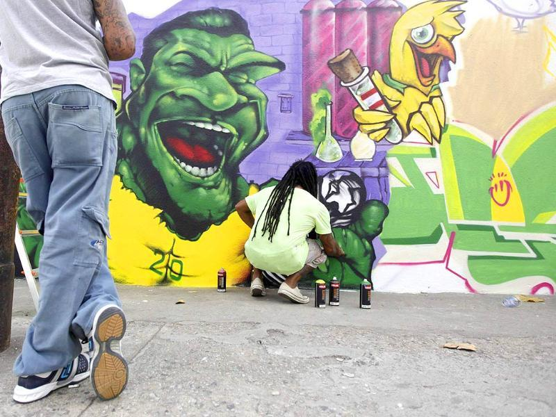 Graffiti artist Raios works on a mural depicting Brazilian footballer Hulk in celebration of the 2014 World Cup in Rio de Janeiro. (Reuters Photo)
