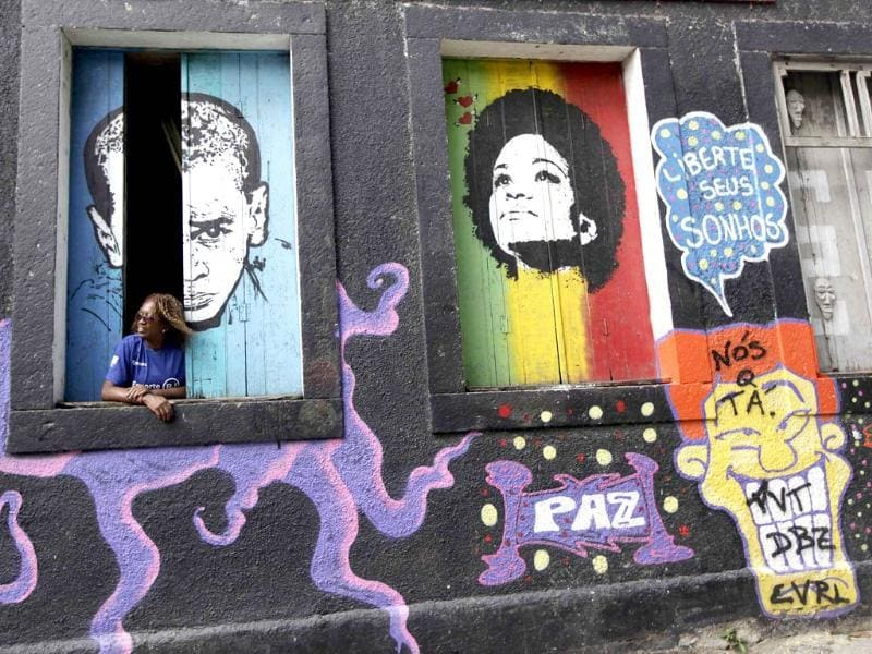 A woman looks out of a window of a graffiti covered house in the Providencia slum in Rio de Janeiro. (Reuters Photo)