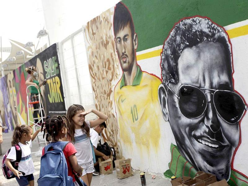 Children look at a graffiti mural by artist Tot depicting Brazilian Neymar (L) and Samba music legend Cartola, in celebration of the 2014 World Cup, in Rio de Janeiro. (Reuters Photo)