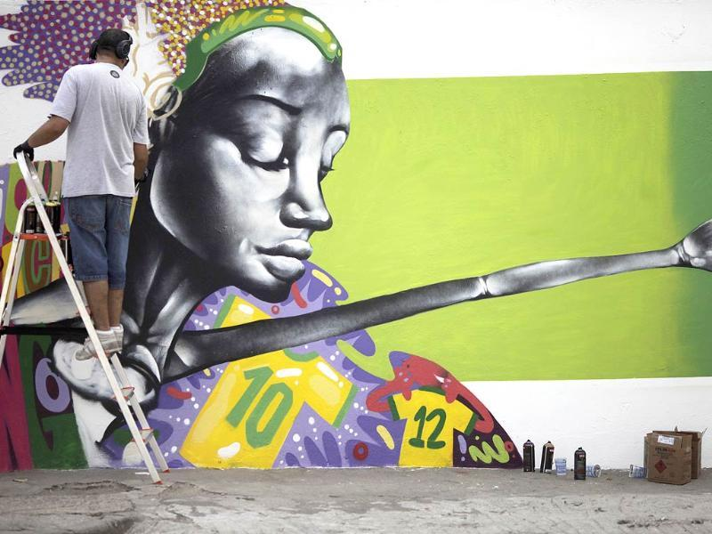 Graffiti artist Barba works on a mural in celebration of the 2014 World Cup, in Rio de Janeiro. (Reuters Photo)