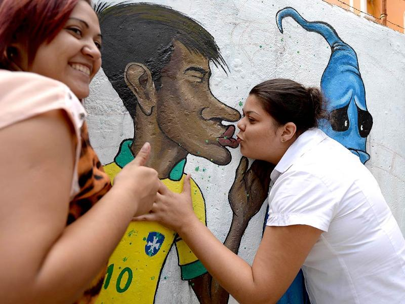 Fans kiss a graffiti depicting footballer Neymar kissing goodbye the ghost of the Maracanazo (the defeat of Brazil by the winning Uruguayan team in the 1950 World Cup) in Rio de Janeiro. (AFP photo)