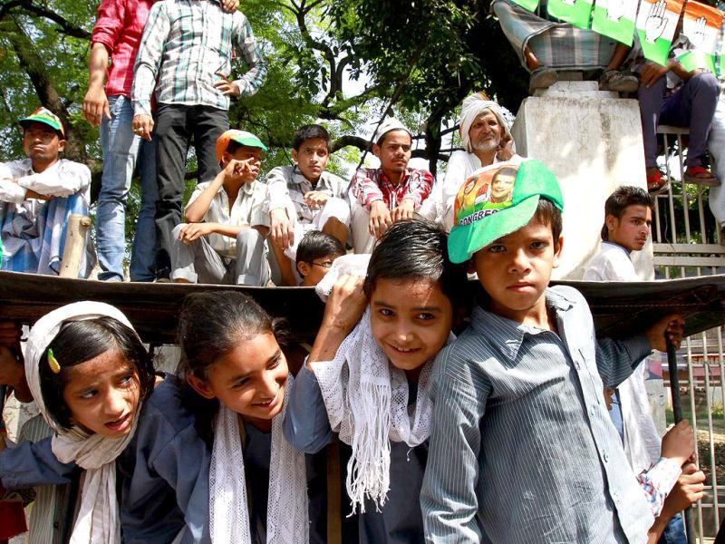School children look on as Congress vice-president Rahul Gandhi leads a roadshow supporting party's Varanasi candidate Ajay Rai. (HT photo/Ajay Aggarwal)