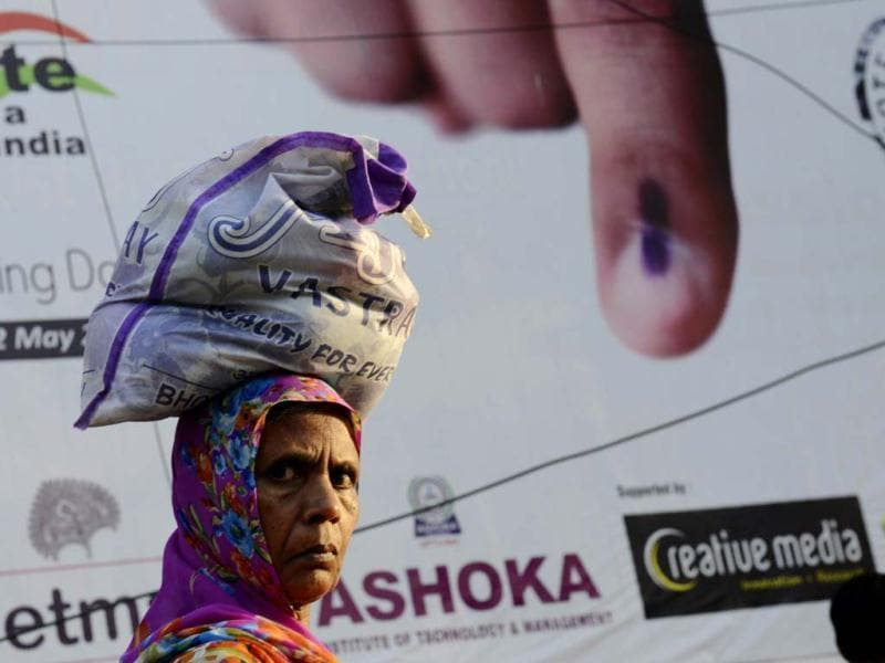 A pedestrian carries a bag over her head as she walks past a banner urging people to vote in Varanasi . (AFP)