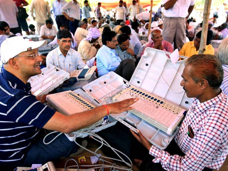 Election officers check their Electronic Voting Machines (EVM) at a distribution centre, in Varanasi . (Ajay Aggarwal / HT Photo)