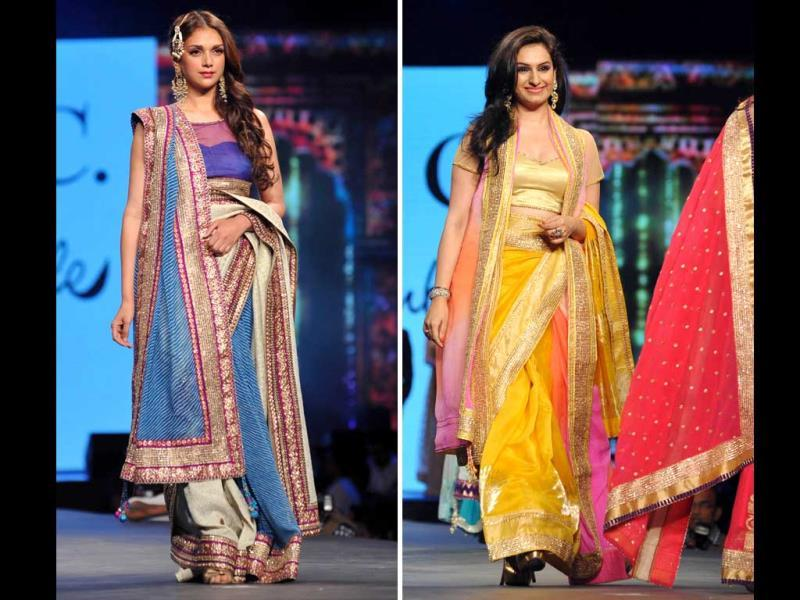 Actor Aditi Rao Hydari and playback singer Akriti Kakkar display a creation by designer Shaina NC during the fashion show. (AFP)