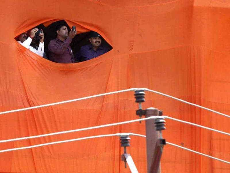 Bhartiya Janata Party supporters peak out of torn flag for a glimpse of party's prime ministerial candidate Narendra Modi as he heads to file his nomination in Varanasi, Uttar Pradesh. (Arvind Yadav/HT Photo)