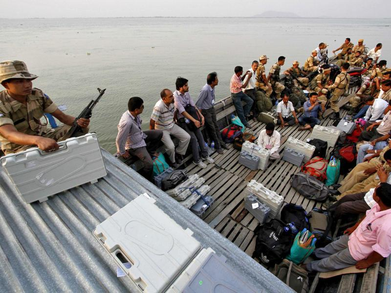 EC officials with EVMs and security personnel travel in a boat to reach polling stations ahead of the sixth phase of LS polls in Assam. Ethnic violece broke out in the state after the elections ended. (Reuters photo)