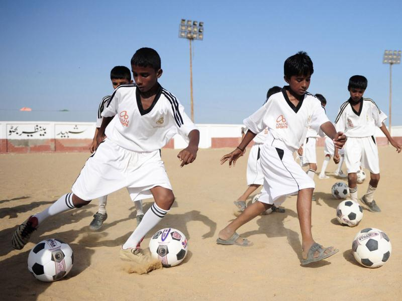 Pakistani local youth participate in a training session on a dusty pitch in a Karachi slum in the famous white shirt of Real Madrid. (AFP Photo)