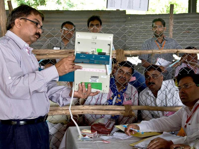 An Indian election official shows the results on an Electronic Voting Machine (EVM) to polling agents at a counting centre in Ghaziabad. (AFP Photo)