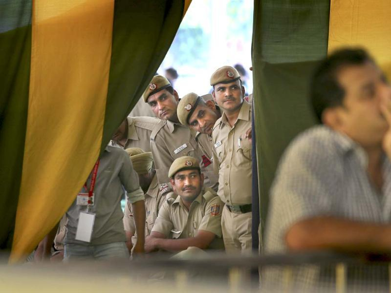 Policemen on duty watch election results on television at a counting station in New Delhi. (AP Photo)