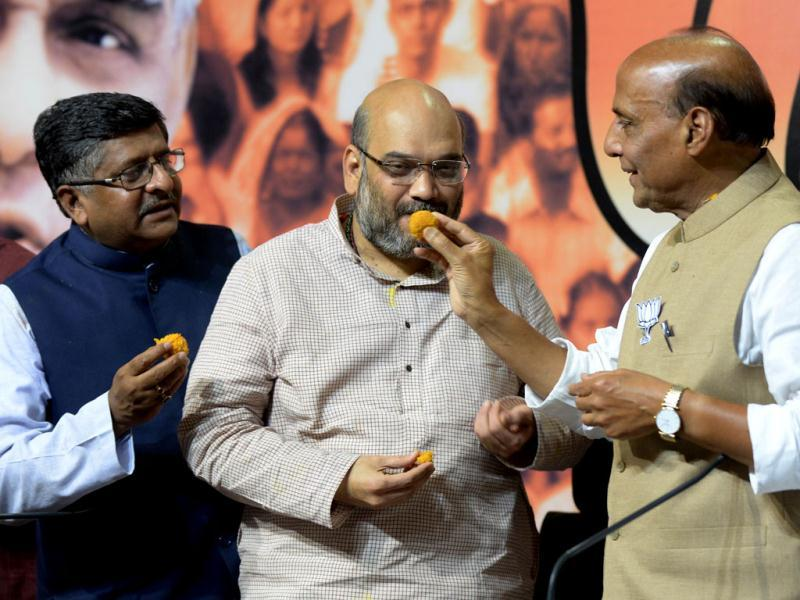 Senior BJP leaders, Ravi Shankar Prasad, Amit Shah and party president Rajnath Singh offer sweets to each other before a press conference at BJP headquarters in New Delhi. (AFP)