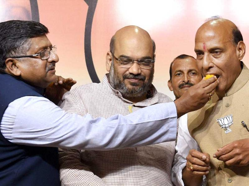 BJP leader Ravi Shankar Prasad offers sweets to party president Rajnath Singh as BJP's UP election incharge Amit Shah looks on during a press conference after the party's huge victory in the Lok Sabha elections. (PTI Photo)