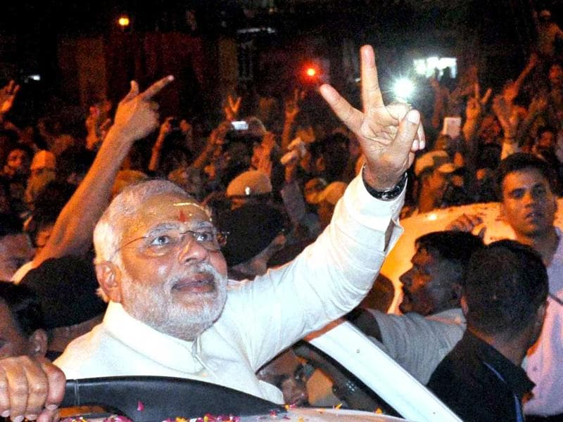 Narendra Modi flashes victory sign during a road show after performing Ganga Aarti in Varanasi on Saturday. (PTI Photo)