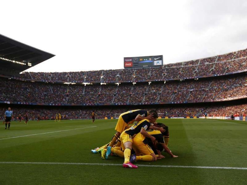 Atletico Madrid's Diego Godin (obscured) is congratulated by teammates after scoring against Barcelona during their La Liga match at Camp Nou stadium in Barcelona. (Reuters Photo)