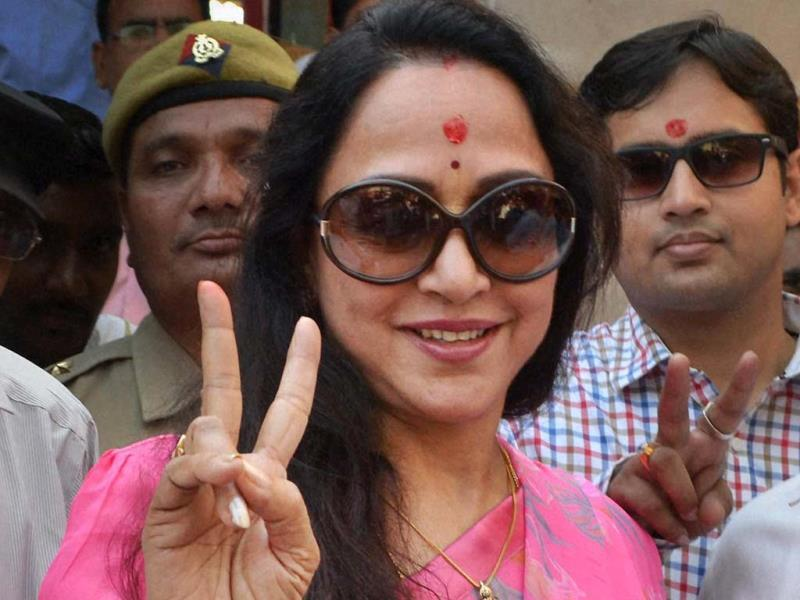 Bollywood actress and BJP candidate Hema Malini waves victory sign as she arrives at a counting station in Mathura on Friday. (PTI Photo)