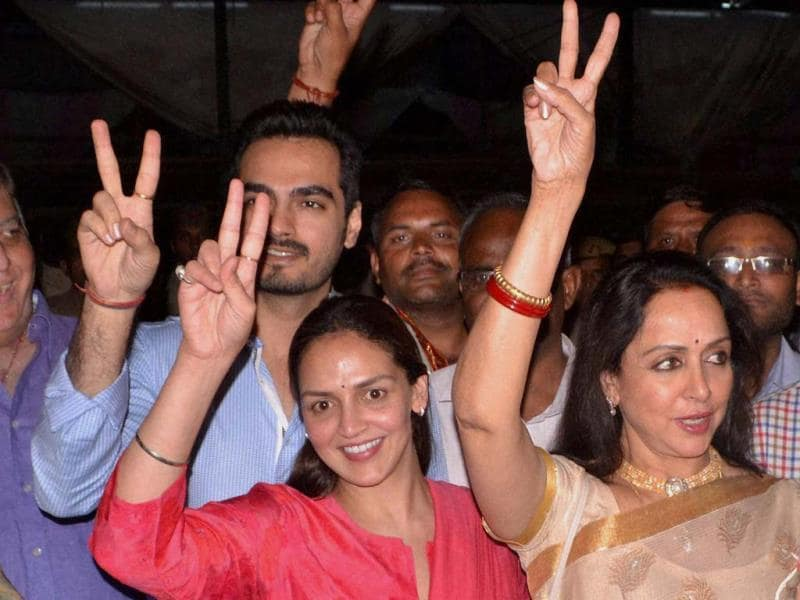 Bollywood actress & BJP candidate Hema Malini flashes victory sign along with her daughter Esha Deol and son-in-law Bharat after winning the Lok Sabha elections, in Mathura on Friday. (PTI Photo)