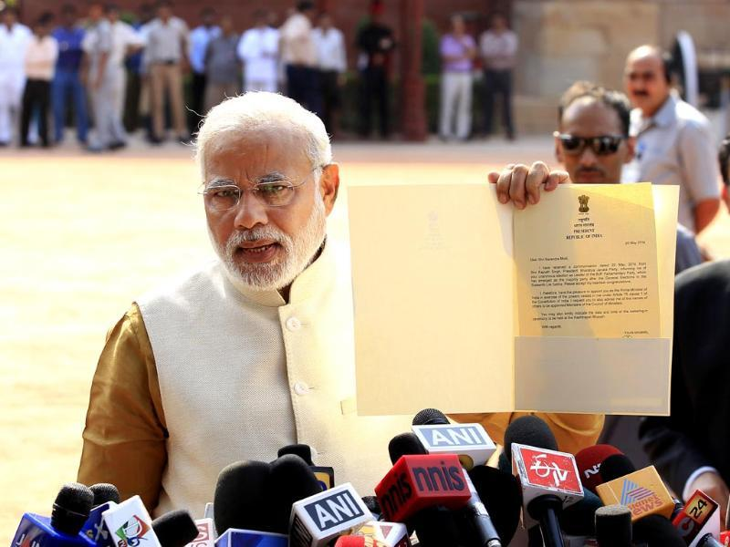 NDA Prime Minister-elect Narendra Modi displays the letter to the media persons that he received from President Pranab Mukherjee during their meeting at the Rashtrapati Bhawan, in New Delhi (Ajay Aggarwal/HT photo)