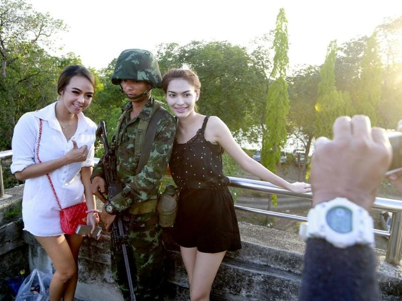Passersby have their photograph taken with a Thai soldier guarding a pedestrian overfly near the site where pro-government demonstrators stage a rally on the outskirts of Bangkok. Thailand's army declared martial law. (AP photo)