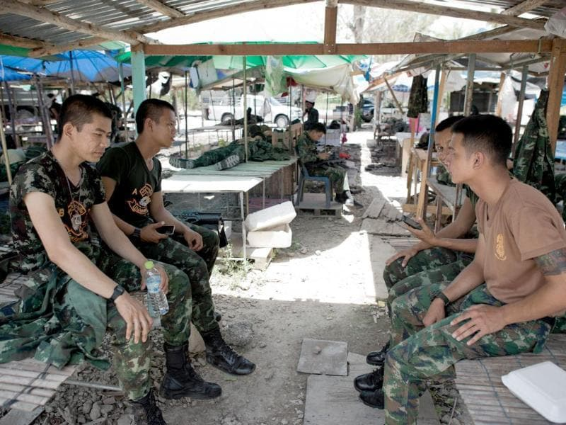 Thai army soldiers take a break from checkpoint near where pro-government 'Red shirts' have been rallying for days on the outskirts of Bangkok. (AFP photo)
