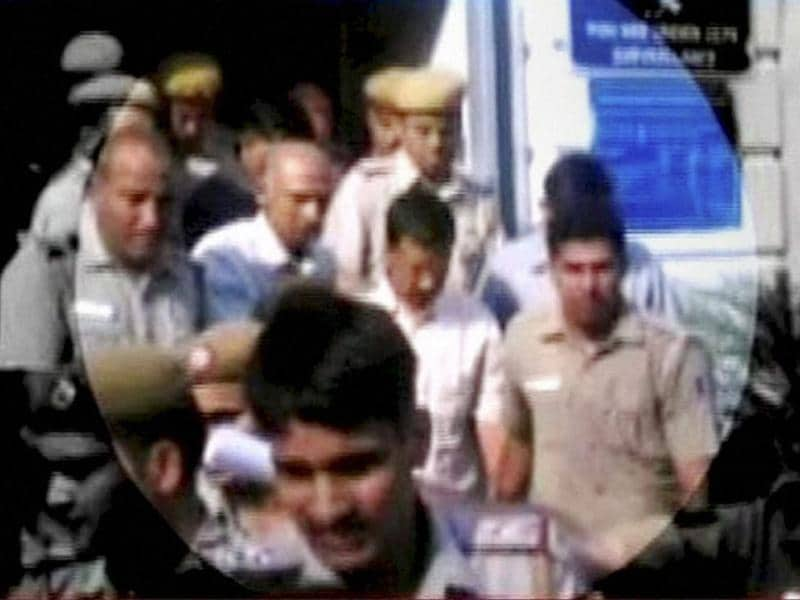 AAP chief Arvind Kejriwal is escorted at Patiala House Courts in New Delhi on Wednesday after a court ordered him to judicial custody for two days in connection with the defamation complaint filed against him by BJP leader Nitin Gadkari. (PTI photo)