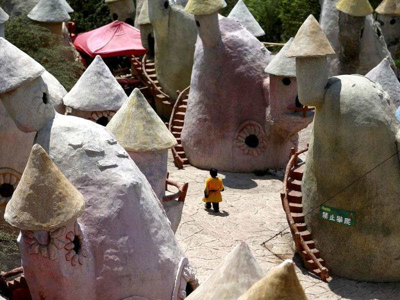 A dwarf walks in between mushroom-shaped houses after performances at Kunming World Butterflies Garden, Yunnan province. (Reuters)
