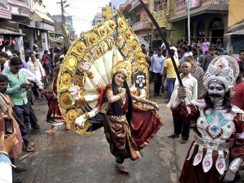 An artist dressed as goddess Durga performs during a procession on the occasion of Chandan Yatra festival in Puri, Bhubaneswar. (AP Photo)
