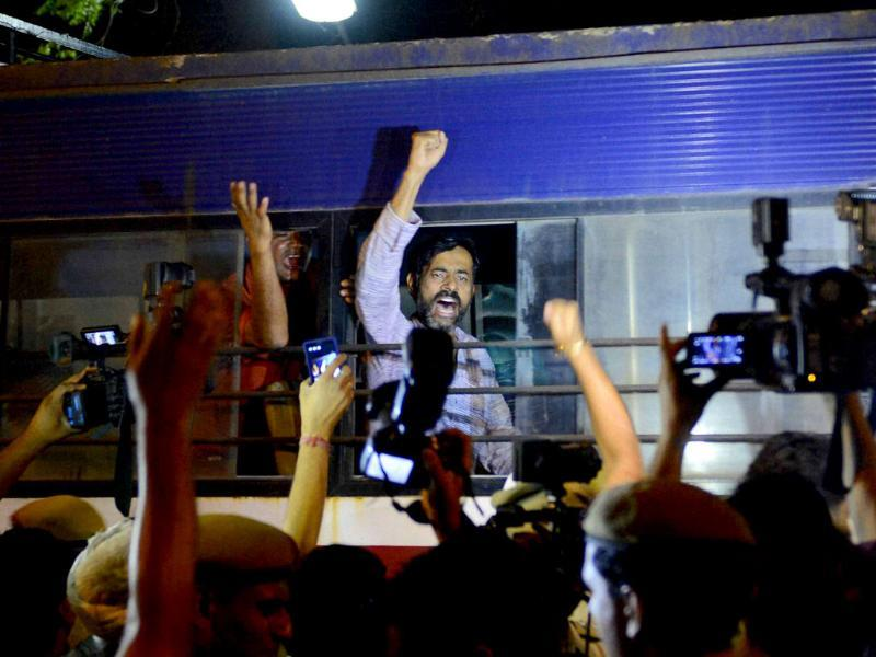 Aam Aadmi Party leader Yogendra Yadav shouts as he taken in police bus during a protest outside Tihar Prisons over the arrest of party chief Arvind Kejriwal in New Delhi. (PTI Photo)