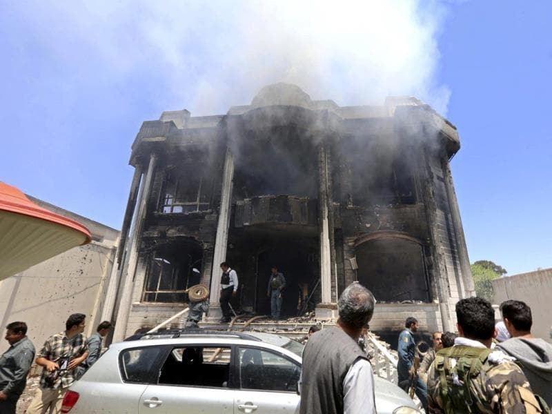 Afghan security officers investigate near smoke rising from a residential building, where insurgents were holed up in, after an attack on the Indian consulate in Herat province. (Reuters)