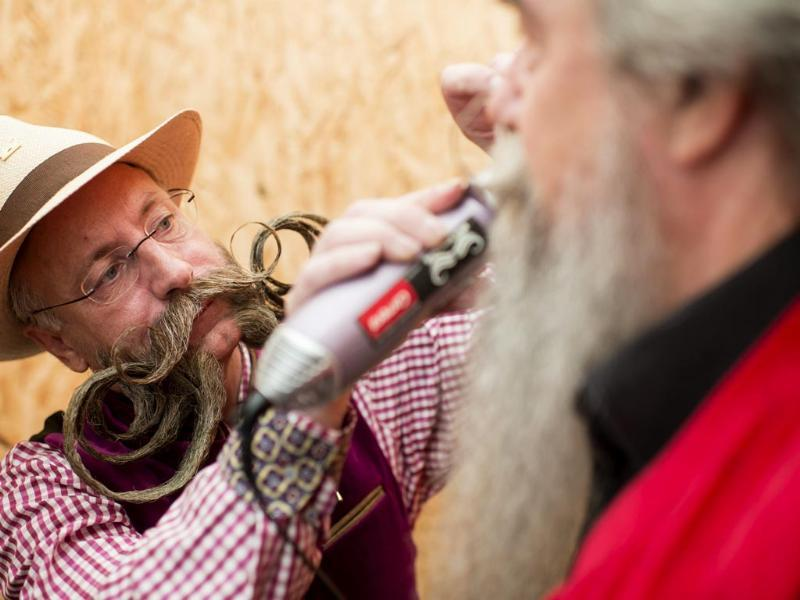 Juergen (L) helps a co-competitor during the European Beard and Moustache Championships in Urdorf, Switzerland (EPA Photo)