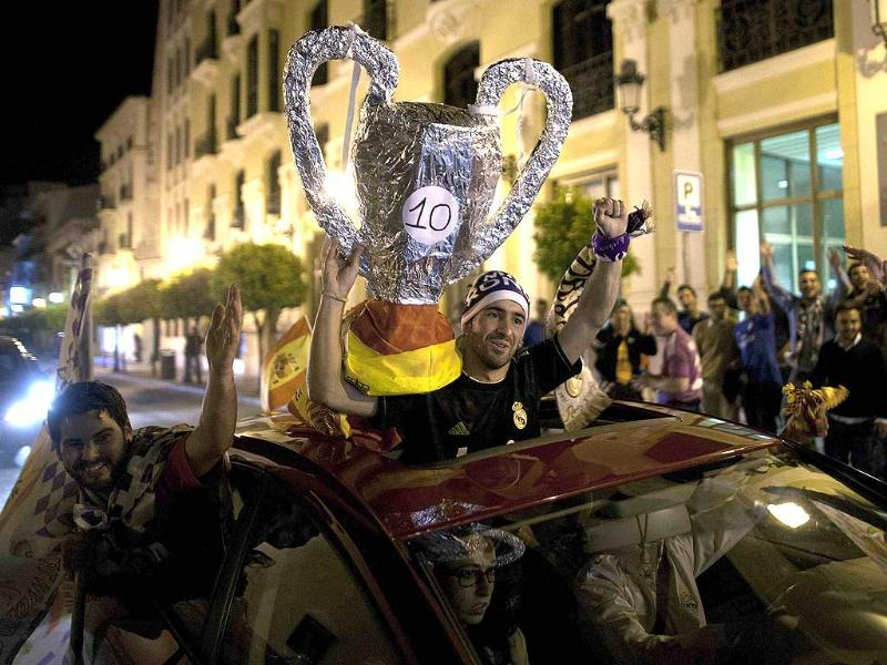 Real Madrid supporters hold up a replica of the Champions League trophy as they celebrate their victory after their Champions League final match against Atletico Madrid, at the Cibeles Square in Madrid. (Reuters Photo)