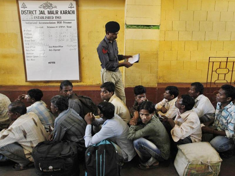 A Pakistani police officer checks the documents of an Indian fishermen waiting for their release from a prison in Karachi. (AP Photo)