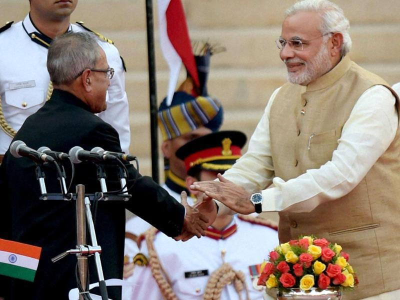 President Pranab Mukherjee greets Prime Minister Narendra Modi after administering him the oath at a ceremony at Rashtrapati Bhavan in New Delhi. (PTI photo)